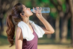 Asian young woman drinking water after jogging,healty and sport concept.