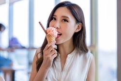 asian young woman eat ice cream dessert in waffle cone at restaurant