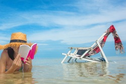 asian young woman enjoy reading a book laying on the sea water of beach, relax and happy comfort in holidays vacation sunbath on the sea beach with deck beach chair along