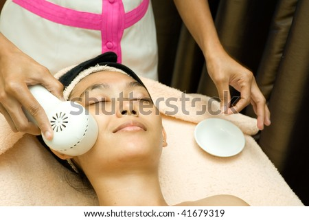 asian young woman having her face being applied by collagen serum in facial treatment session at beauty clinic