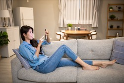 asian young woman is using smart phone and lying on couch leisurely in living room at home