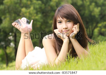 Asian young woman lying on the green grass and smilling