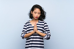 Asian young woman over isolated blue background keeps palm together. Person asks for something