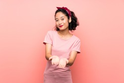 Asian young woman over isolated pink background holding copyspace imaginary on the palm to insert an ad