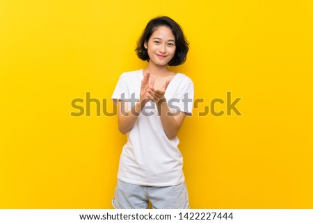 Asian young woman over isolated yellow wall applauding after presentation in a conference #1422227444