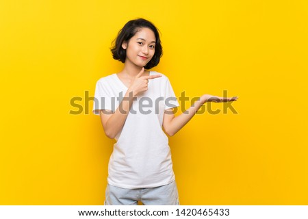 Asian young woman over isolated yellow wall holding copyspace imaginary on the palm to insert an ad