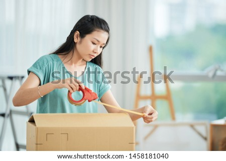 Asian young woman packing the cardboard box with adhesive tape she moving the new house ストックフォト ©