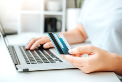 Asian young woman resting and browsing internet with Laptop holding credit card online shopping concept