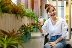Asian young woman sitting at co-working space office during a break, holding cold beverage plastic glass in hand with smiling and cheerful face. Relaxing zone for worker with green area