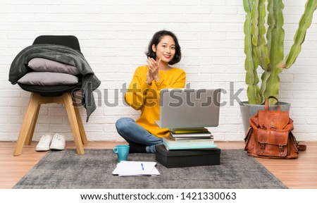 Asian young woman sitting on the floor applauding #1421330063
