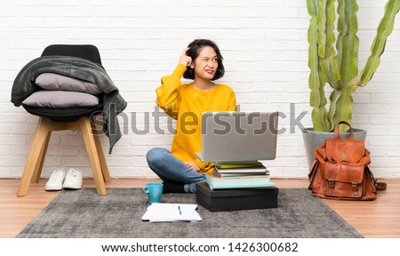 Asian young woman sitting on the floor having doubts and with confuse face expression Photo stock ©