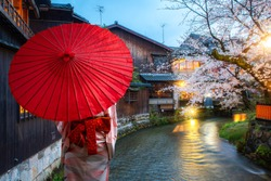 Asian young woman traveller wearing japanese traditional kimono with red umbrella sightseeing at famous destination cherry blossom at Shirakawa River in the Gion District at night in Kyoto, Japan.