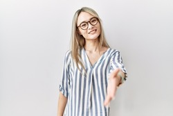 Asian young woman wearing casual clothes and glasses smiling friendly offering handshake as greeting and welcoming. successful business.