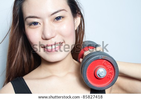 Asian young woman with dumbbells