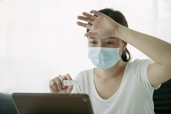 Asian young woman with hygiene protective face mask using SARS 2019-nCoV COVID-19 coronavirus antigen rapid test kit - ag test kit at home and consulting a testing result with doctor via video call.