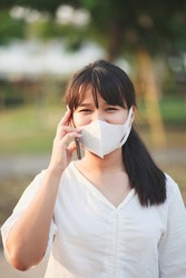 asian younger woman wearing protection mask talking on mobilephone