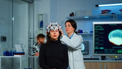 Asistance of neurological doctor putting eeg headset on patient head scaning brain functions, descovering diagnosis of disease. Team of scientists researchers working late night in neurology clinic