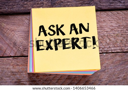 Ask an expert. Top view of working place with ask an expert lettering at notepad. #1406653466