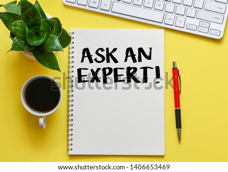 Ask an expert. Top view of working place with ask an expert lettering at notepad. #1406653469