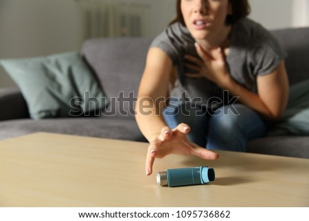 Asmathic girl catching inhaler having an asthma attack sitting on a couch in the living room at home