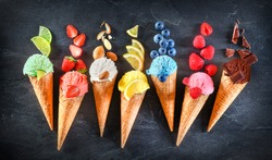 Asorted of ice cream scoops with cones in row on black background. Colorful set of ice cream scoops of different flavours. Sweet icecream like chocolate, lemon, lime, almond, strawberries, vanilla.