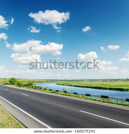 aspalt road near river under cloudy sky