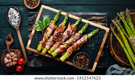Asparagus baked with bacon and spices. Healthy food. Top view. Free space for your text. Stock photo ©