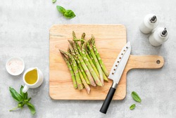 Asparagus cooking concept, top down view on a cutting board with fresh bunch of asparagus, lying down on a kitchen table, spring healthy cooking idea