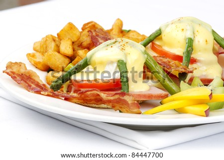 Asparagus ham tomato eggs benedict with fresh fruit and hashbrowns