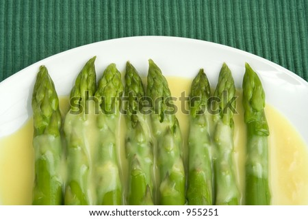Asparagus spears with Hollandaise sauce drizzled over them.