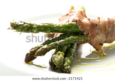 Asparagus wrapped in bacon topped with olive oil