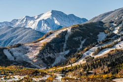 Aspen, Colorado buttermilk or highlands famous ski slope hill peak in rocky mountains view on sunny day with snow on yellow foliage autumn trees