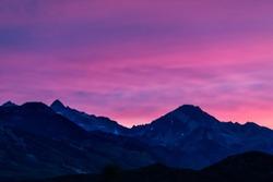 Aspen, Colorado colorful purple pink blue vivid vibrant sunset twilight with Snowmass mountain peak ridge closeup silhouette