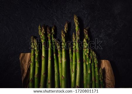 Asperges vertes fraîches sur fond noir en ardoise. Fresh green asparagus on black slate background. Top view. Flat lay vegetables. Photo stock ©