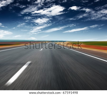 Asphalt blurred road and blue sky with clouds