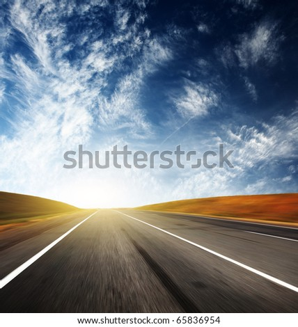 Asphalt blurred road and sunlight and blue sky with clouds