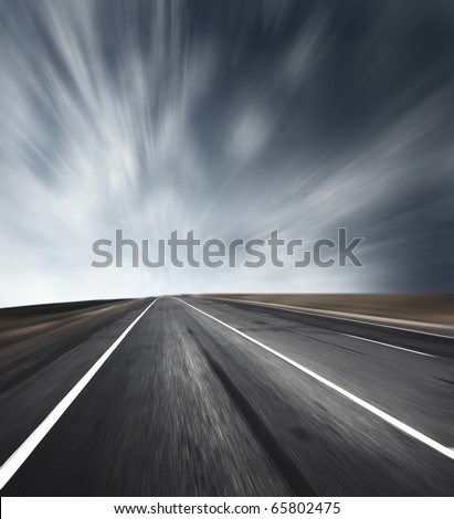 Asphalt blurred road with sunlight on a horizon and dark sky with clouds
