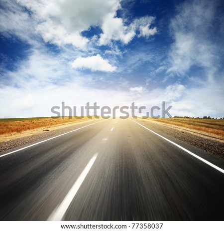 Asphalt blurry road and bright blue sky with clouds