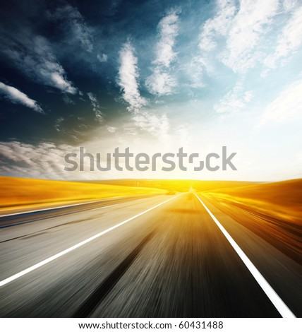 Asphalt blurry road and sky with clouds
