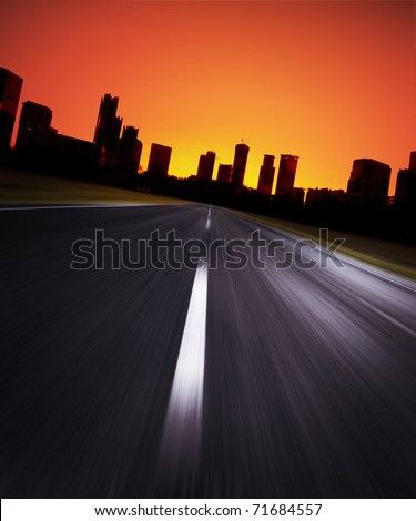 Asphalt blurry road with city silhouette on a horizon and red sunrise sky