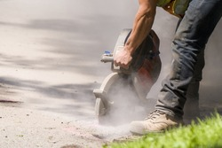 Asphalt cutter. A worker cuts through an asphalt road with a large handheld rotary cutter. Lots of dust from cutting. Worker not identifiable, only arm and leg visible. Room for text.