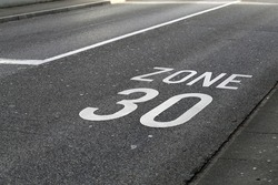 Asphalt driveway in Switzerland with 30km/h speed limit. Speed limit marked to road with text
