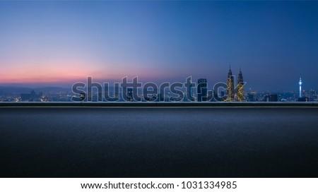 Asphalt empty road side with   Kuala Lumpur city skyline background . Night scene .