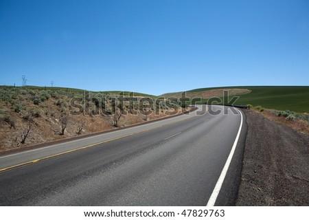Asphalt highway winding on spring hills