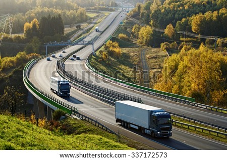 Asphalt highway with electronic toll gates in autumn woodland. Three trucks on the road. The bridge spanning the valley. View from above. Sunny day with bright fall colors. #337172573