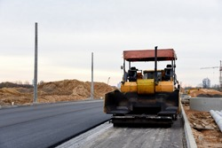 Asphalt paver machine during road work. Road Machinery at construction site for paving works. Screeding the sand for road concreting. Asphalt pavement is layered over concrete pavement. Road Surfacing