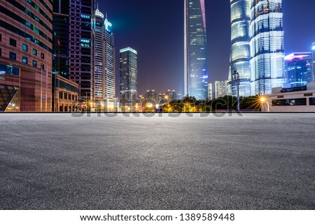 Asphalt race track and modern skyline and buildings in Shanghai at night