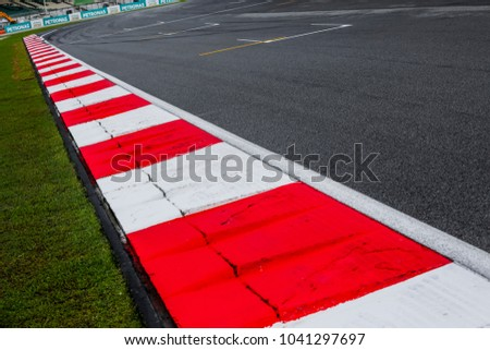 Asphalt red and white kerb of a race track detail. Motorsports racing circuit close up. #1041297697