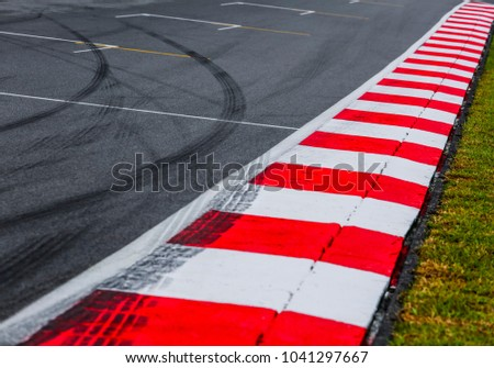 Asphalt red and white kerb of a race track detail with tire marks. Motorsports racing circuit close up.  #1041297667