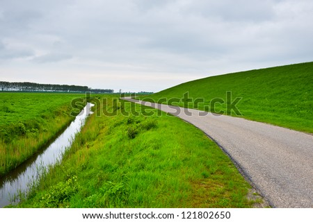 Asphalt Road along Protective Dam and Canal in the Netherlands